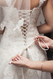 Dressing the bride dresses. Many hands holding on to each other in a group Stock Image