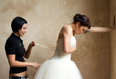 Dressing the bride with tattoo Stock Image