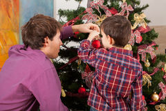 Dressing the Christmas tree Stock Images