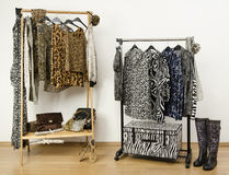Dressing closet with animal print clothes arranged on hangers and accessories. Royalty Free Stock Photos