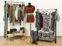 Dressing closet with animal print clothes arranged on hangers. Red cheetah print outfit on a mannequin. Colorful wardrobe with jungle pattern clothes and Stock Images