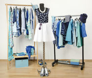 Dressing closet with blue clothes arranged on hangers. Cute summer outfit on a mannequin. Stock Images