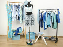 Dressing closet with blue clothes arranged on hangers and an outfit on a mannequin. Royalty Free Stock Photography