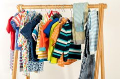 Dressing closet with clothes arranged on hangers. stock image