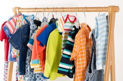 Dressing closet with clothes arranged on hangers. stock images