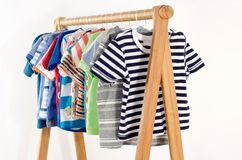 Dressing closet with clothes arranged on hangers. royalty free stock photos