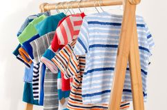 Dressing closet with clothes arranged on hangers. stock photos