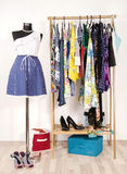 Dressing closet with colorful clothes arranged on hangers and a Stock Photography