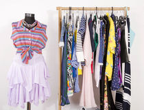 Dressing closet with colorful clothes arranged on hangers and a Royalty Free Stock Photos