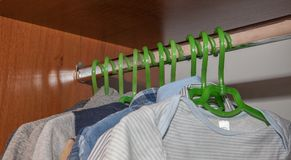 Dressing closet with complementary clothes arranged on hangers.Colorful wardrobe of newborn,kids, babies full of all clothes, shoe Stock Image