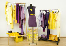 Dressing closet with complementary colors violet and yellow clothes. Royalty Free Stock Photography