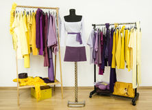 Dressing closet with complementary colors violet and yellow clothes. Stock Photo