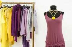 Dressing closet with complementary colors violet and yellow clothes. Royalty Free Stock Photo