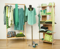 Dressing closet with green clothes arranged on hangers and shelf, dress on a mannequin. Royalty Free Stock Images