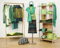 Dressing closet with green clothes arranged on hangers and shelf. Stock Photo