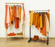 Dressing closet with orange clothes arranged on hangers. Royalty Free Stock Photography