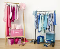 Dressing closet with pink and blue clothes arranged on hangers. Stock Photo