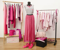 Dressing closet with pink clothes arranged on hangers and an outfit on a mannequin. Royalty Free Stock Image
