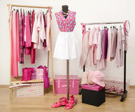 Dressing closet with pink clothes arranged on hangers and an outfit on a mannequin.