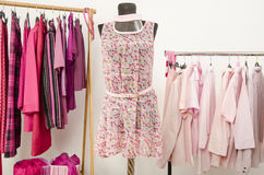 Dressing closet with pink clothes arranged on hangers and an outfit on a mannequin. Stock Images