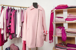 Dressing closet with pink clothes arranged on hangers and shelf, a coat on a mannequin. Stock Photo
