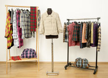 Dressing closet with plaid clothes arranged on hangers and a jacket on a mannequin. Stock Image