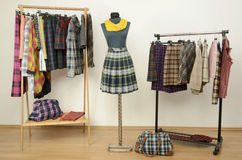 Dressing closet with plaid clothes arranged on hangers and an ou Royalty Free Stock Photo