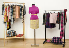 Dressing closet with plaid clothes arranged on hangers and an outfit on a mannequin. Royalty Free Stock Images