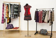 Dressing closet with plaid clothes arranged on hangers and an outfit on a mannequin. Stock Images