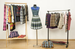 Dressing closet with plaid clothes arranged on hangers and an outfit on a mannequin Royalty Free Stock Photo