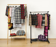 Dressing closet with plaid clothes arranged on hangers on racks. Royalty Free Stock Image