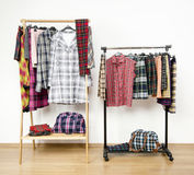 Dressing closet with plaid clothes arranged on hangers on racks. Stock Photos