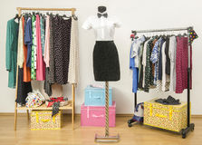 Dressing closet with polka dots clothes arranged on hangers. Stock Photos
