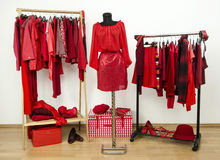 Dressing closet with red clothes arranged on hangers and an outfit on a mannequin. Royalty Free Stock Photo