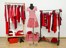 Dressing closet with red and white clothes arranged on hangers and an outfit on a mannequin. Stock Images