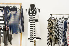 Dressing closet with striped clothes arranged on hangers and a black and white outfit on a mannequin. Stock Images
