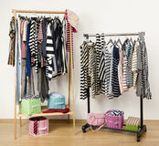 Dressing closet with striped clothes arranged on hangers. Stock Photos