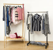 Dressing closet with striped clothes arranged on hangers. Royalty Free Stock Photos