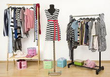 Dressing closet with striped clothes arranged on hangers. Stock Images