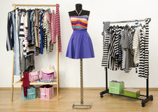 Dressing closet with striped clothes arranged on hangers and an outfit on a mannequin. Stock Images