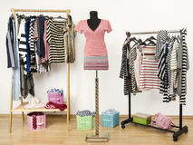 Dressing closet with striped clothes arranged on hangers and an outfit on a mannequin. Stock Photo