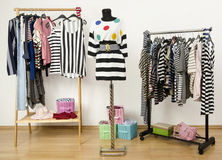 Dressing closet with striped clothes arranged on hangers. Royalty Free Stock Images