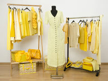 Dressing closet with yellow clothes arranged on hangers and a dr Stock Photos