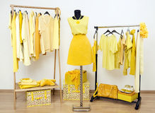 Dressing closet with yellow clothes arranged on hangers and an outfit on a mannequin. Stock Images