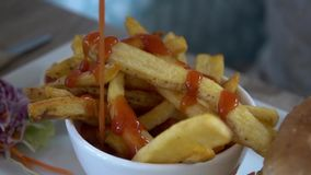 Dressing french fries with ketchup stock footage