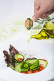 Dressing a gourmet salad with olive oil Royalty Free Stock Photo