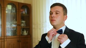 Dressing man straightens bow-tie shallow depth of field. HD stock video