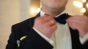 Dressing man straightens bow-tie shallow depth of field. HD stock video footage