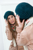 Dressing at mirror. Young beautiful lady trying winter clothes in front of a mirror Stock Photography