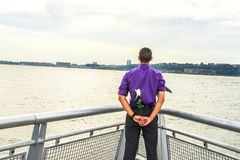 Waiting for You. Dressing in a purple shirt and gray pants, a black tie flowing in the wind, a young guy is standing by a river, holding a white rose behind his Stock Images